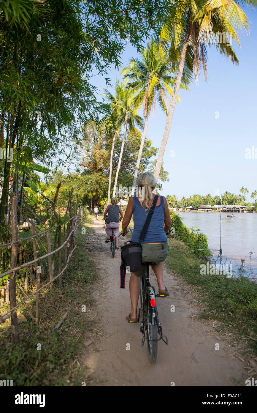Rear view of two female tourists cycling on Mekong riverbank, Don Det, Laos - Stock Image