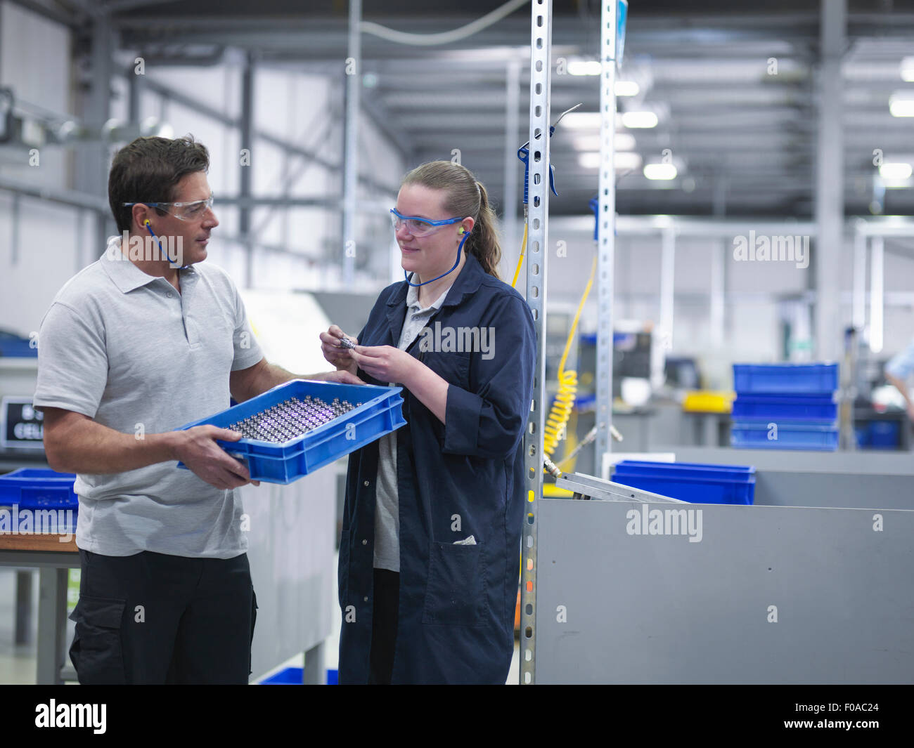 Male and female engineers discussing product - Stock Image