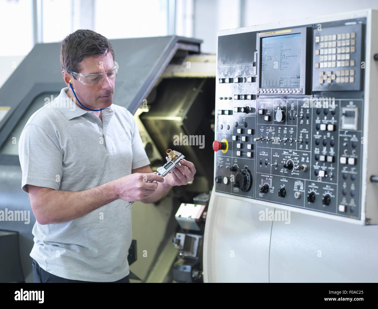 Engineer measuring part in front of CNC lathe - Stock Image