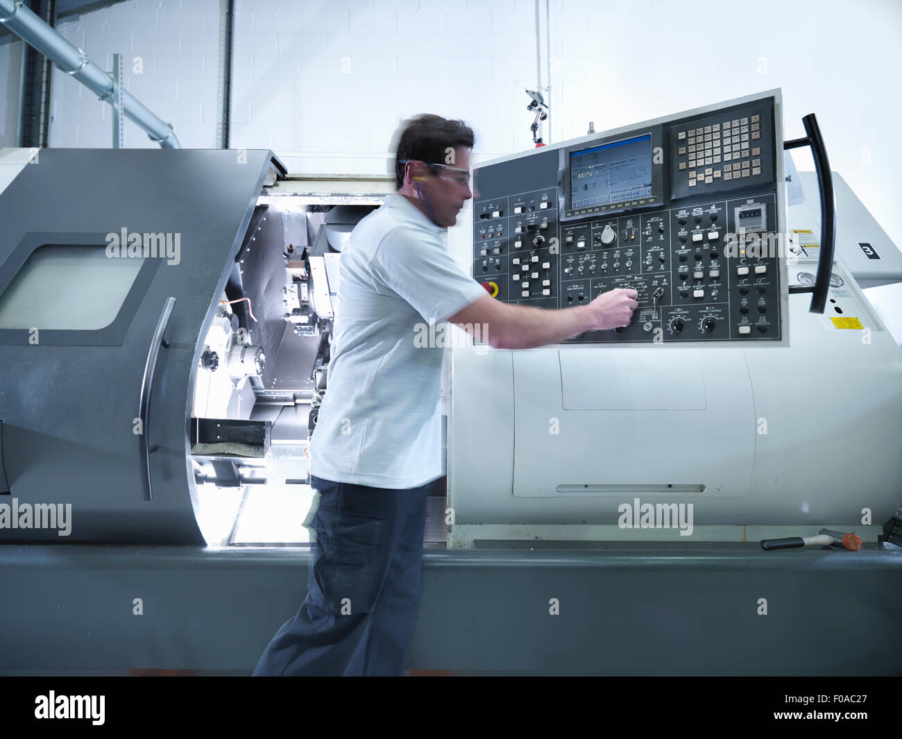 Engineer operating CNC lathe in factory - Stock Image