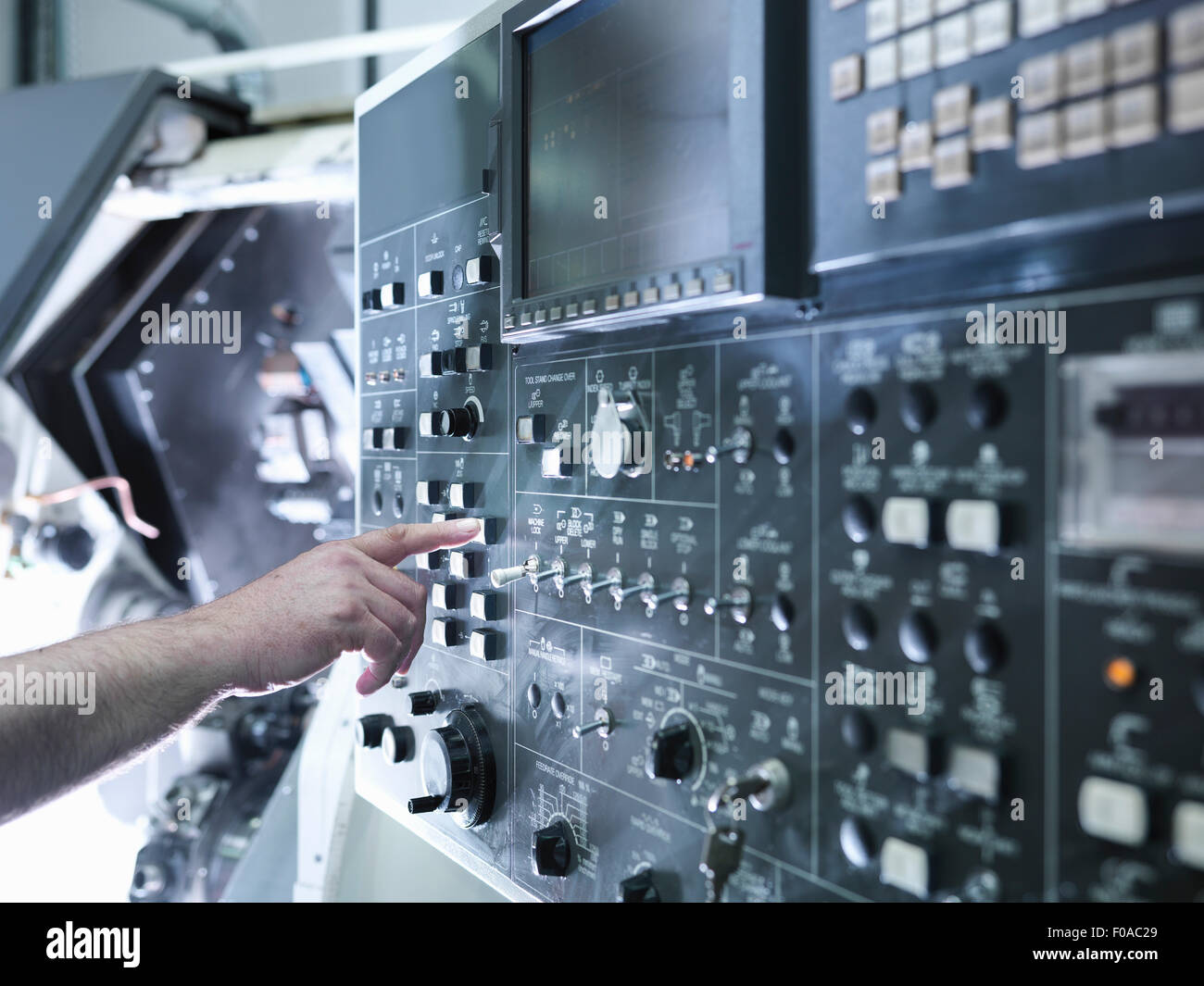 Hand of engineer operating CNC lathe control panel, close up - Stock Image