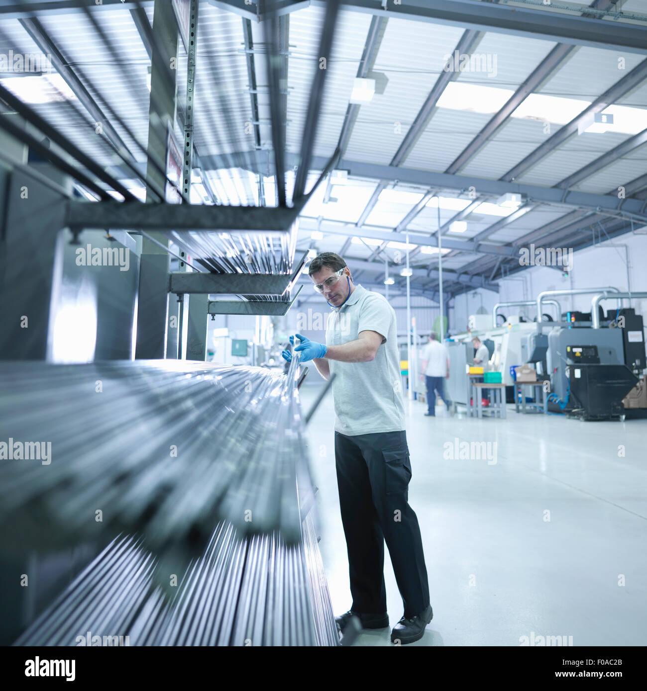 Engineer inspecting steel rods in factory - Stock Image