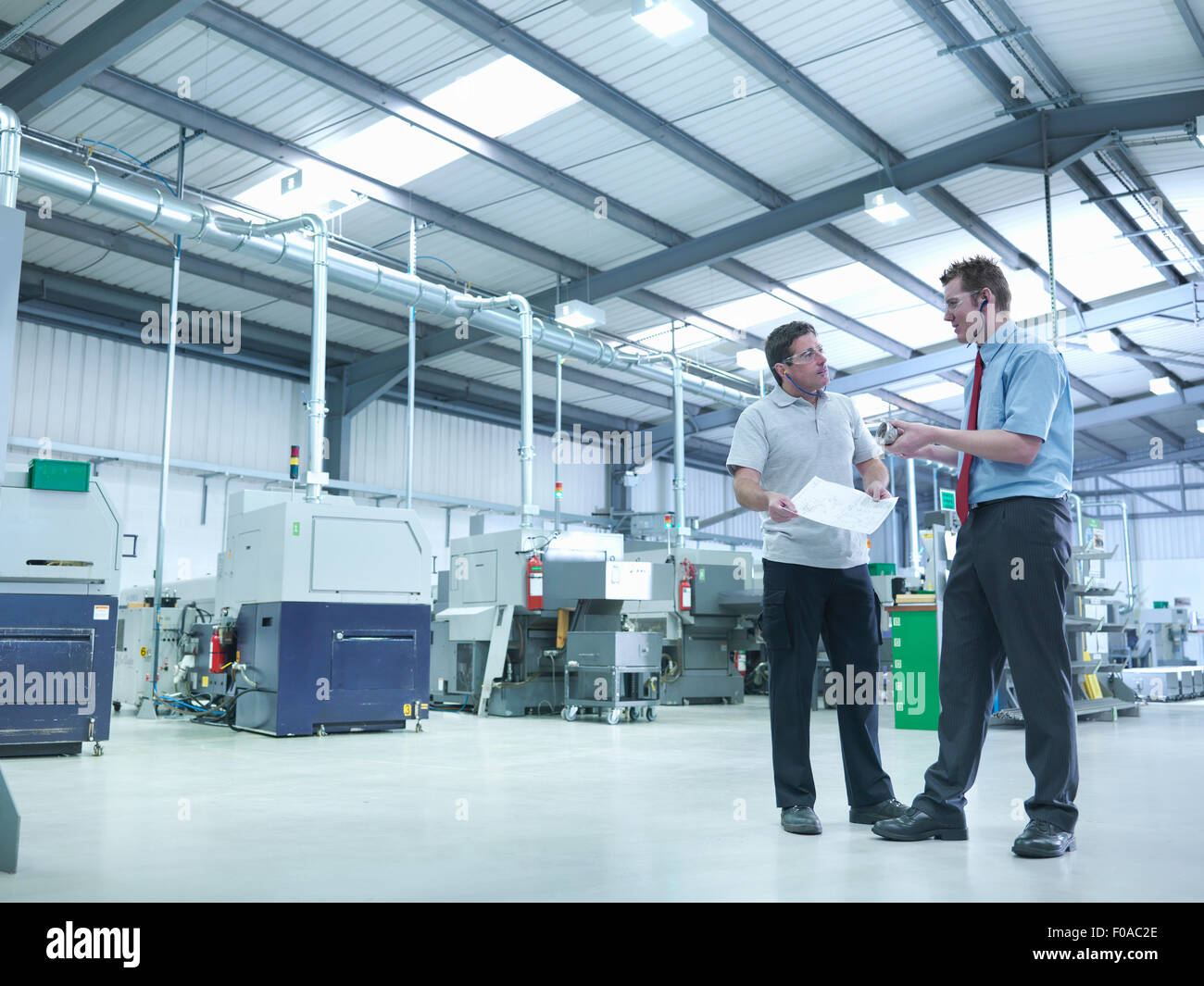 Engineer and apprentice discussing drawings in factory - Stock Image