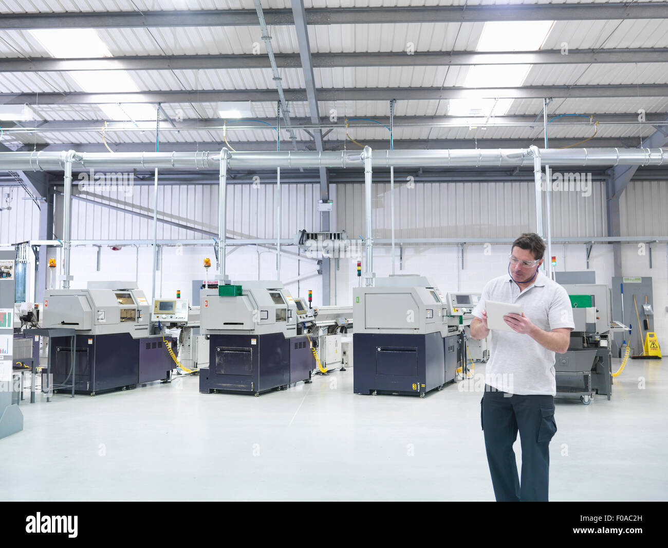 Engineer using digital tablet by production line in factory - Stock Image