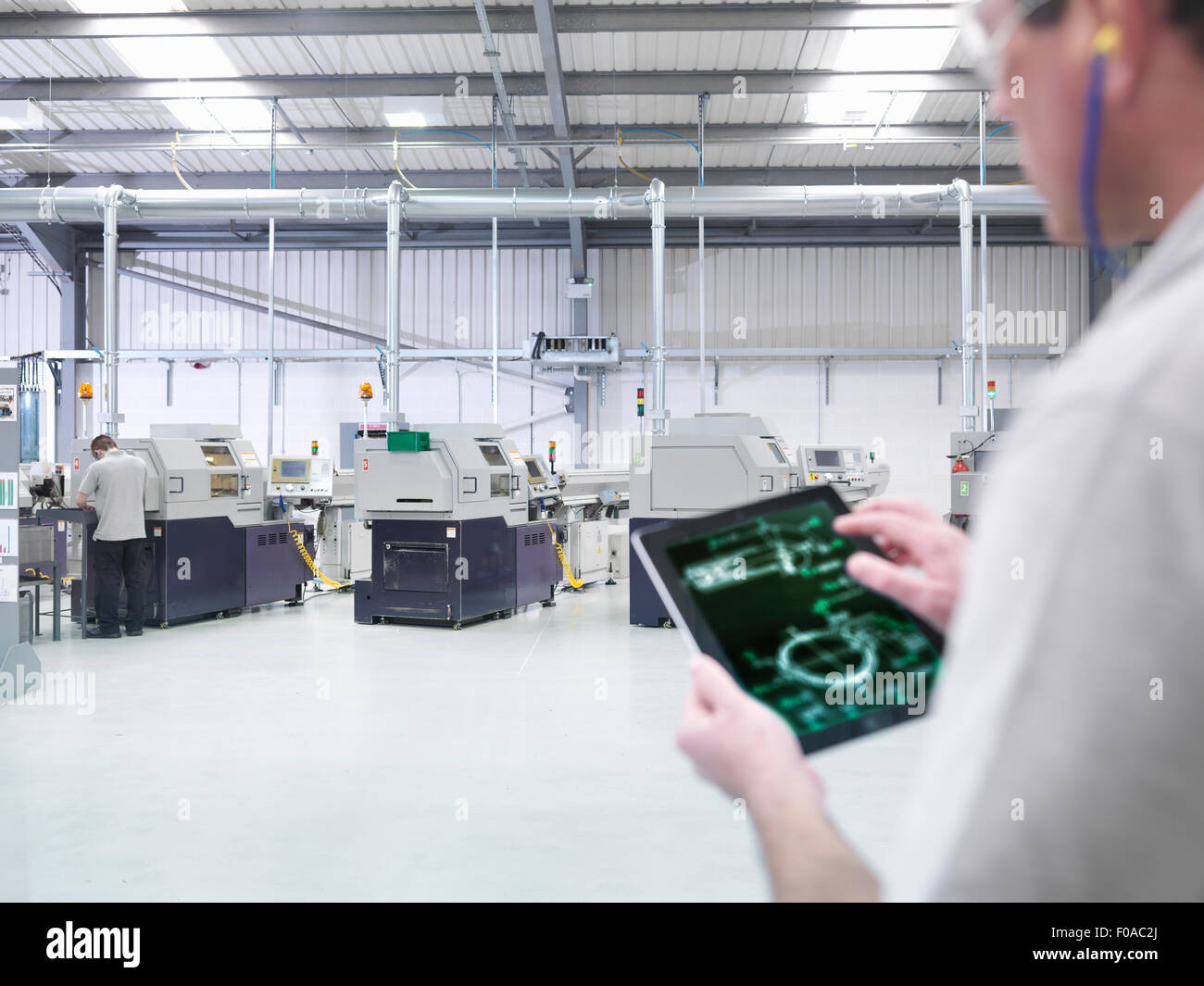 Engineer using digital tablet by production line in factory, close up - Stock Image
