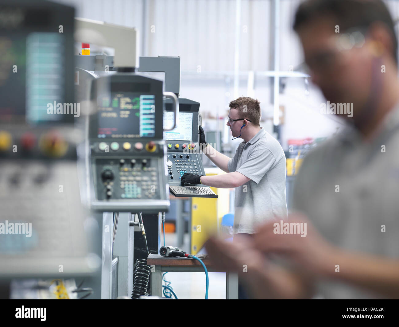 Engineers operating CNC lathes in factory - Stock Image