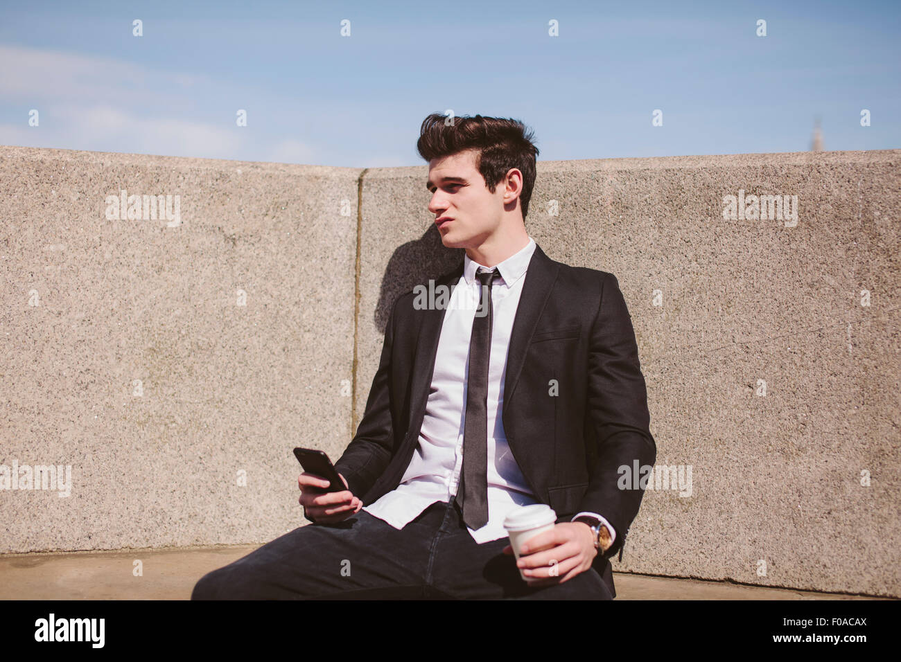 Disappointed young businessman on city seat with smartphone - Stock Image