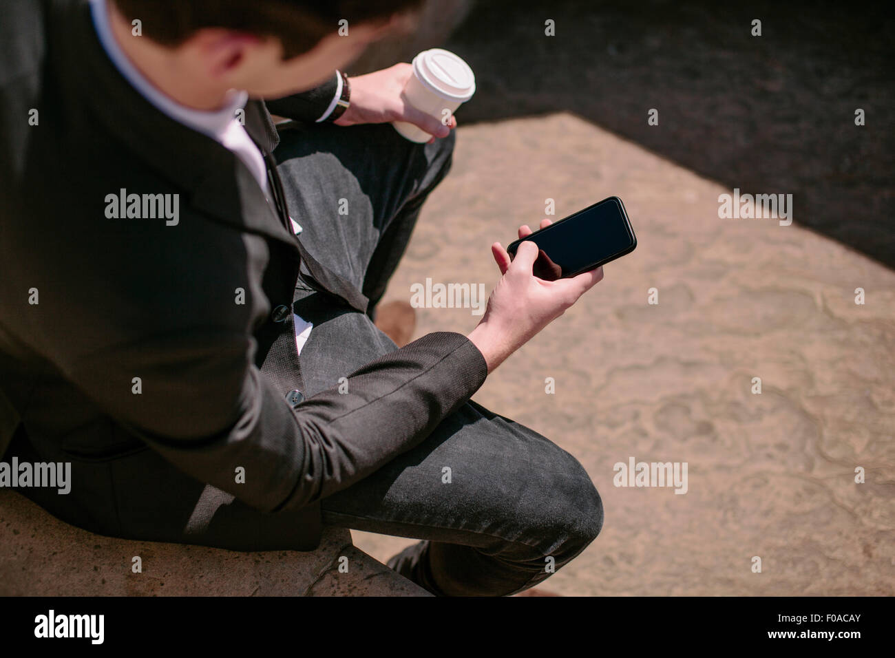 Over the shoulder view of young businessman reading smartphone texts - Stock Image
