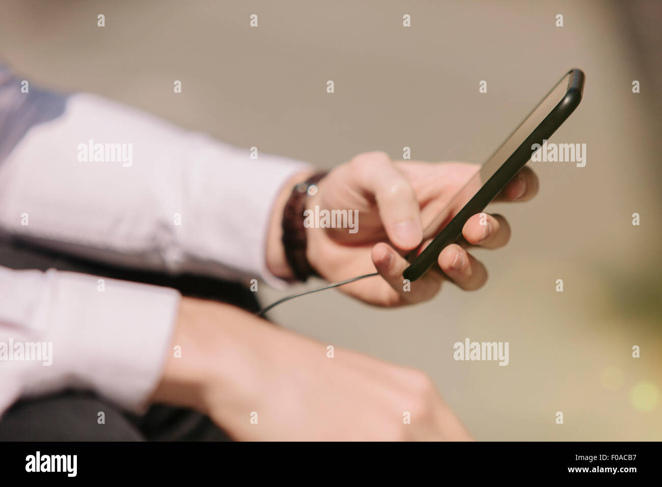 Hands of young businessman selecting music on smartphone - Stock Image