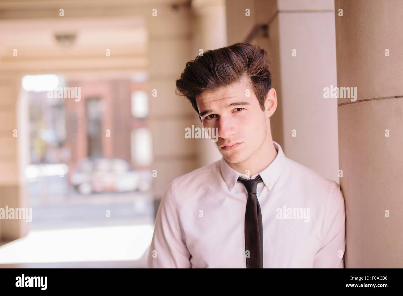 Portrait of confident young city businessman leaning against pillar - Stock Image