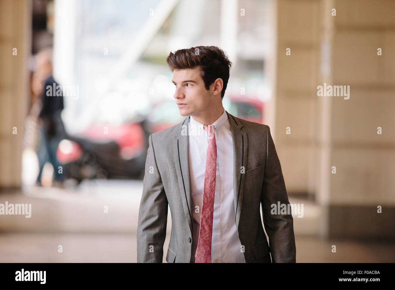 Confident young city businessman walking on sidewalk - Stock Image