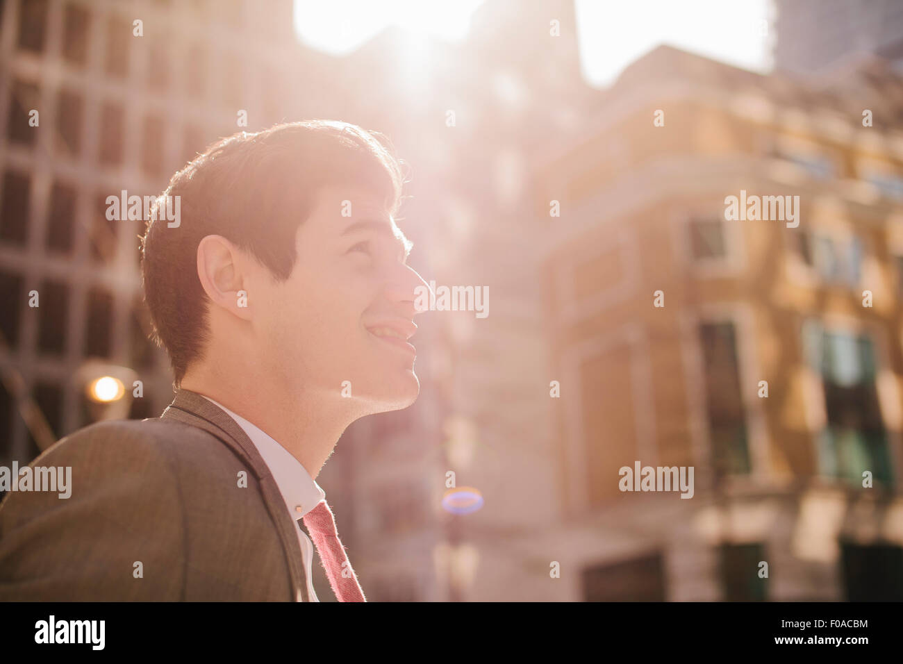 Young city businessman looking up in sunlight Stock Photo