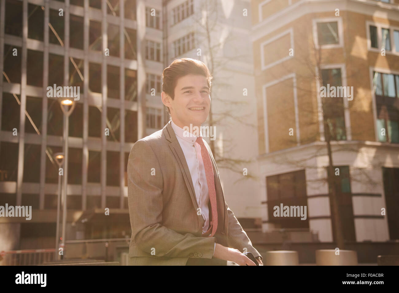 Portrait of young city businessman walking outside office building - Stock Image