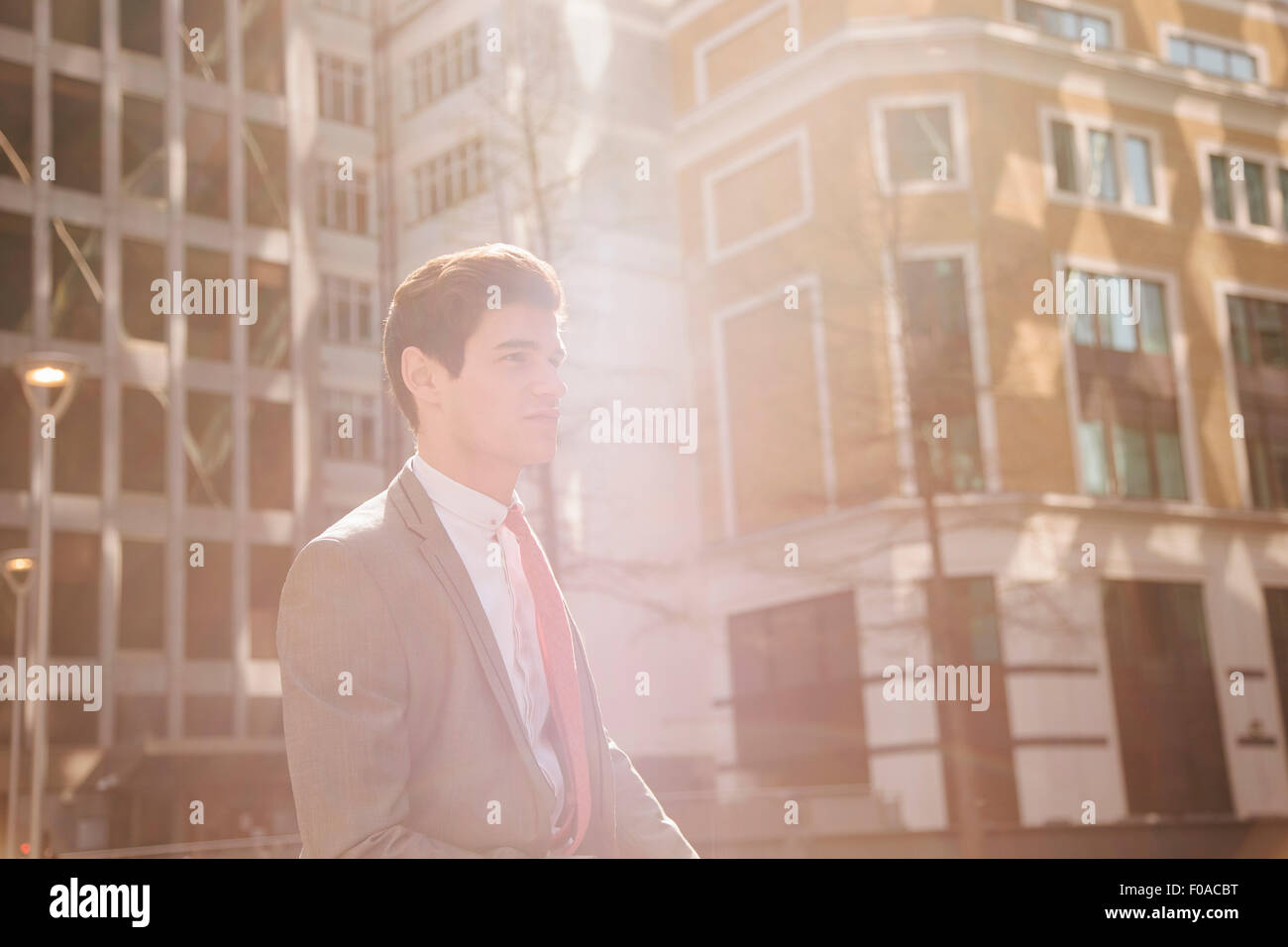 Young city businessman walking outside office building - Stock Image