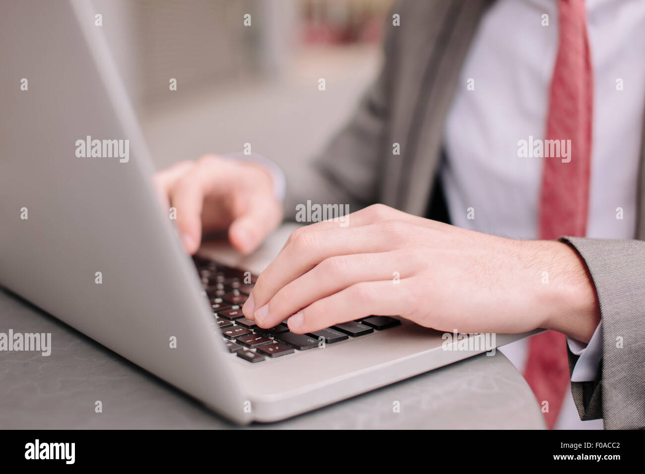 Hands of young city businessman typing on laptop at sidewalk cafe - Stock Image