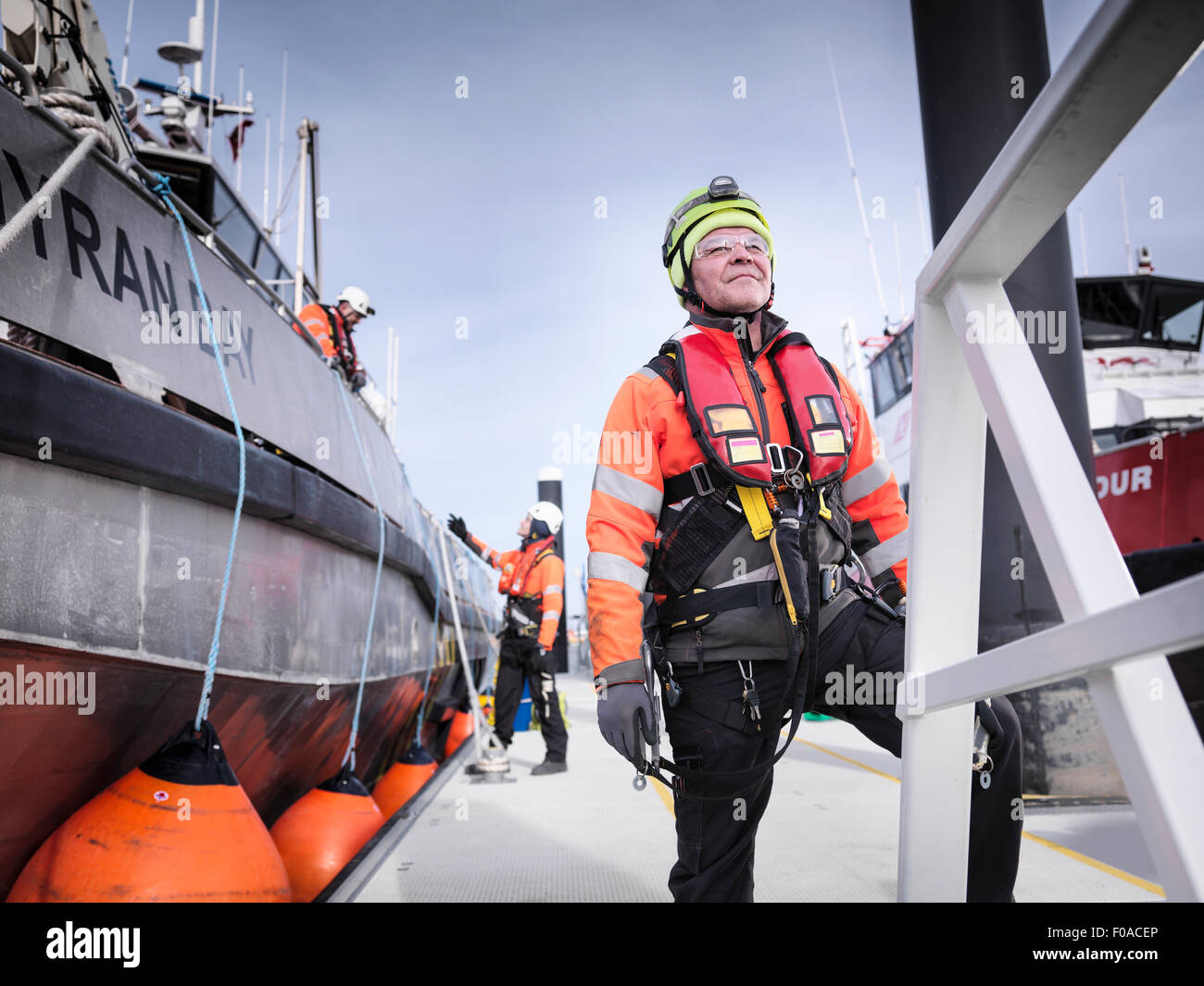 Offshore windfarm engineers in port with boats - Stock Image