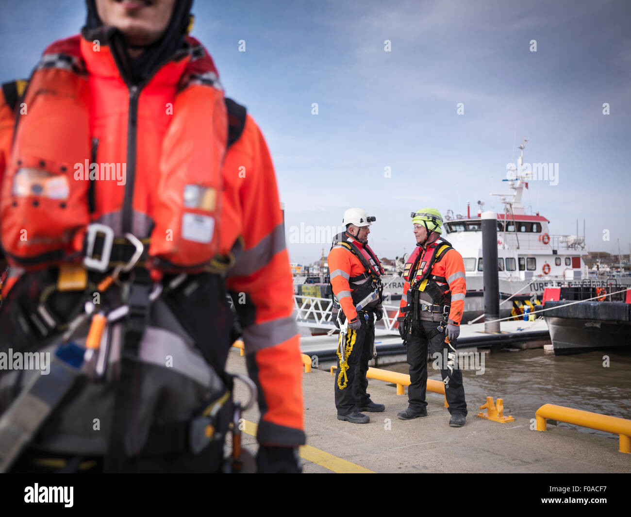 Offshore windfarm engineers on quayside with boats in the background - Stock Image