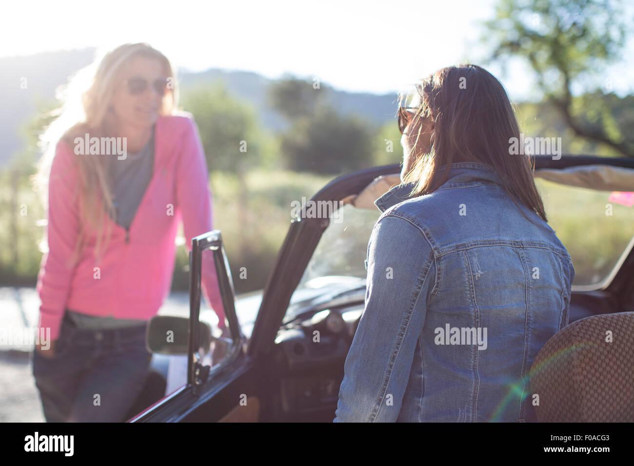 Two mature women, talking, beside convertible car - Stock Image