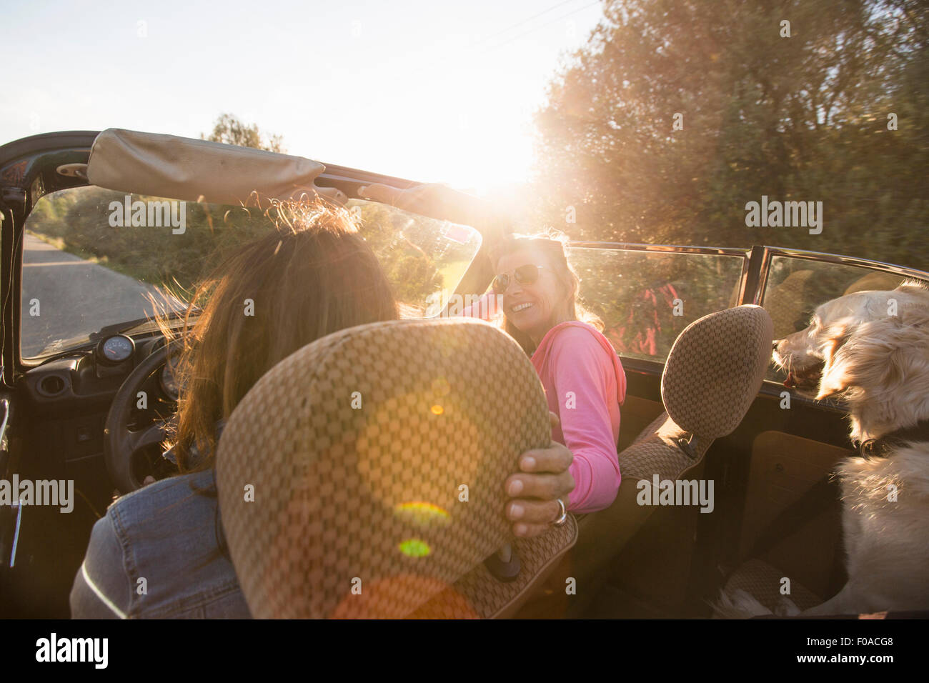 Two mature women in convertible car, rear view - Stock Image