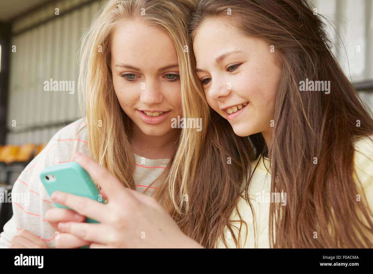Two girls reading smartphone texts in shelter - Stock Image
