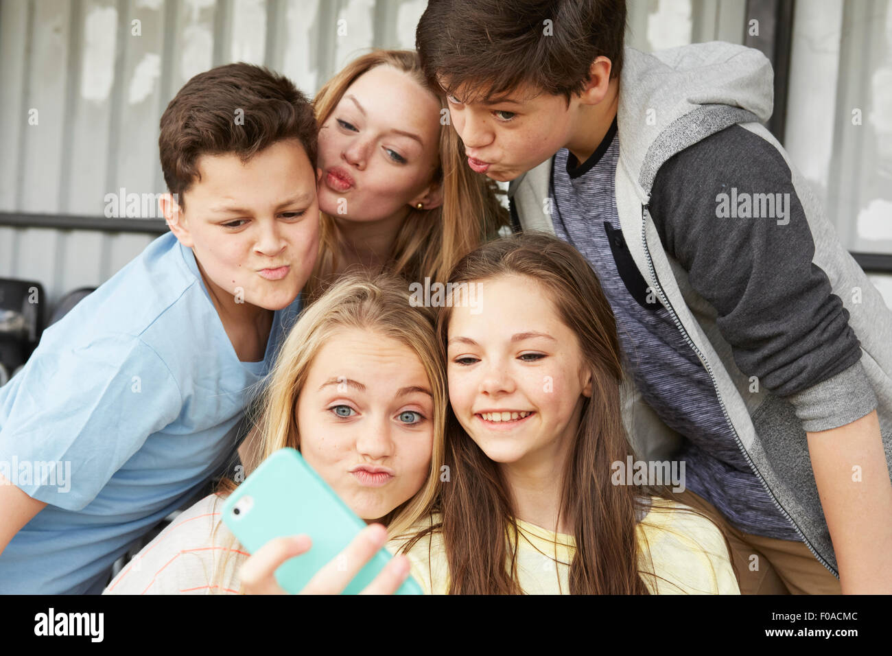 Five boys and girls making faces for smartphone selfie in shelter - Stock Image
