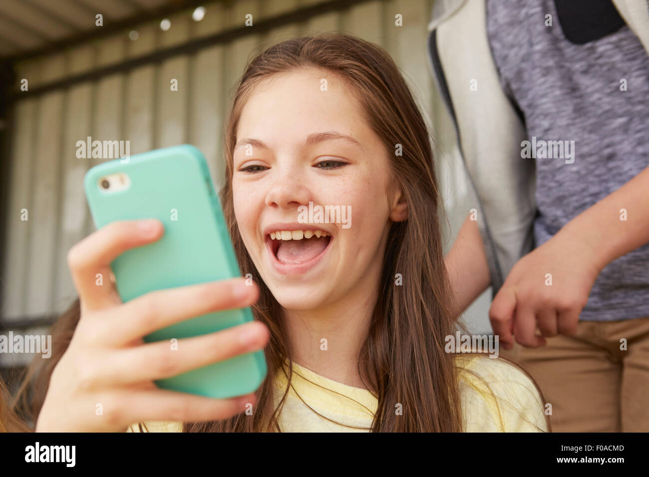 Girls laughing at smartphone in shelter - Stock Image