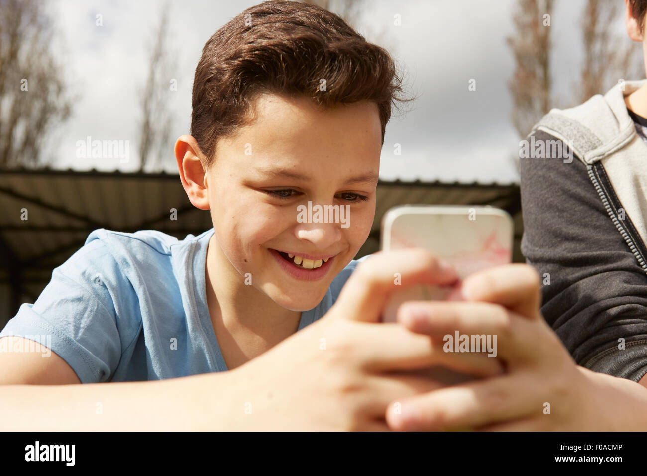 Smiling boy reading smartphone text message - Stock Image