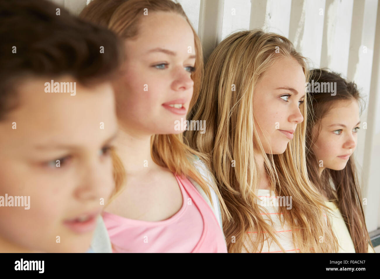 Three girls and boy looking out from shelter - Stock Image