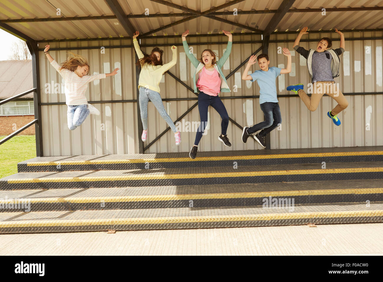 Five boys and girls jumping mid air in stadium stand - Stock Image