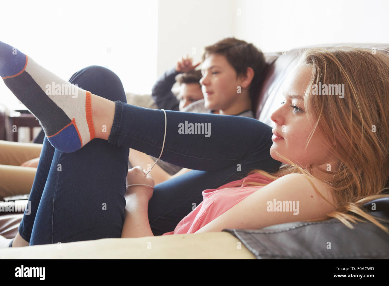 Girl and two boys watching tv from sofa - Stock Image