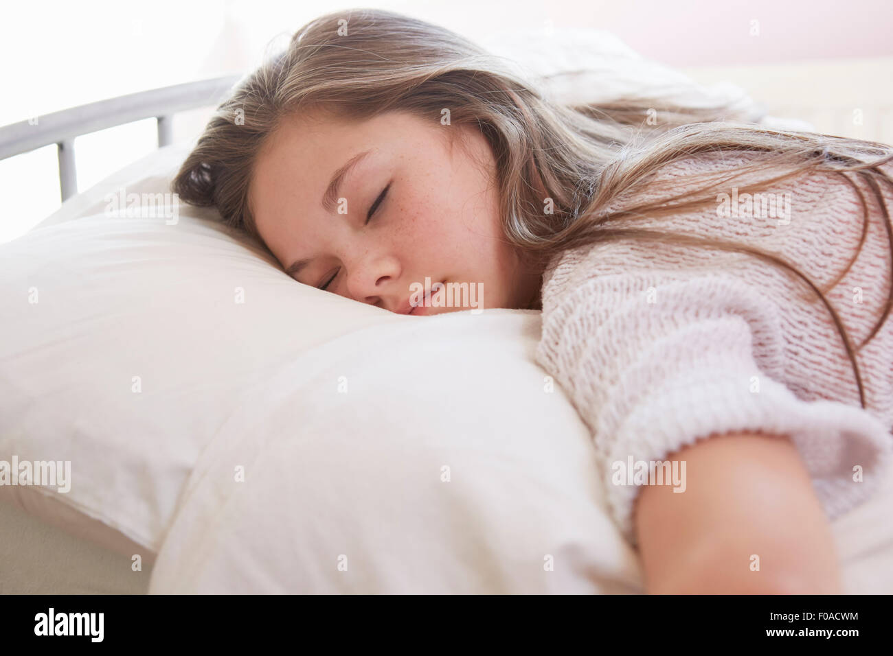 Girl lying on bed asleep - Stock Image