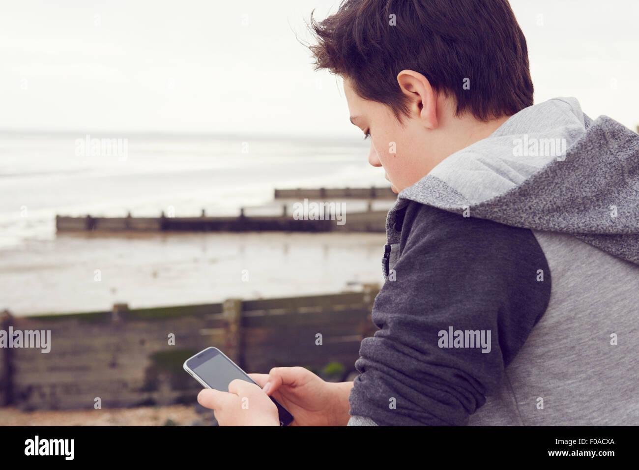 Teenage boy at seaside texting on smartphone, Southend on Sea, Essex, UK - Stock Image
