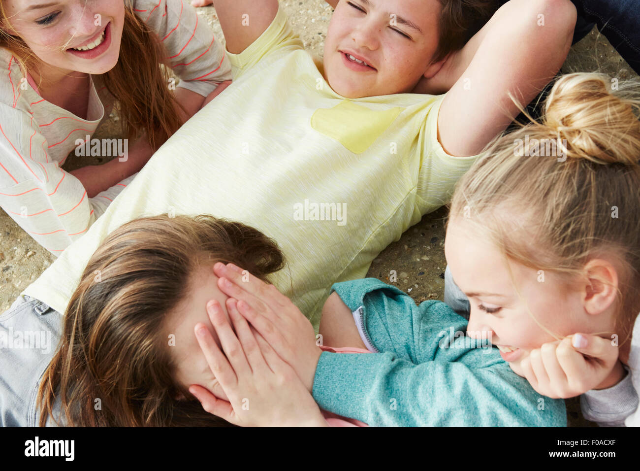 Cropped view of five boys and girls fooling around laughing - Stock Image