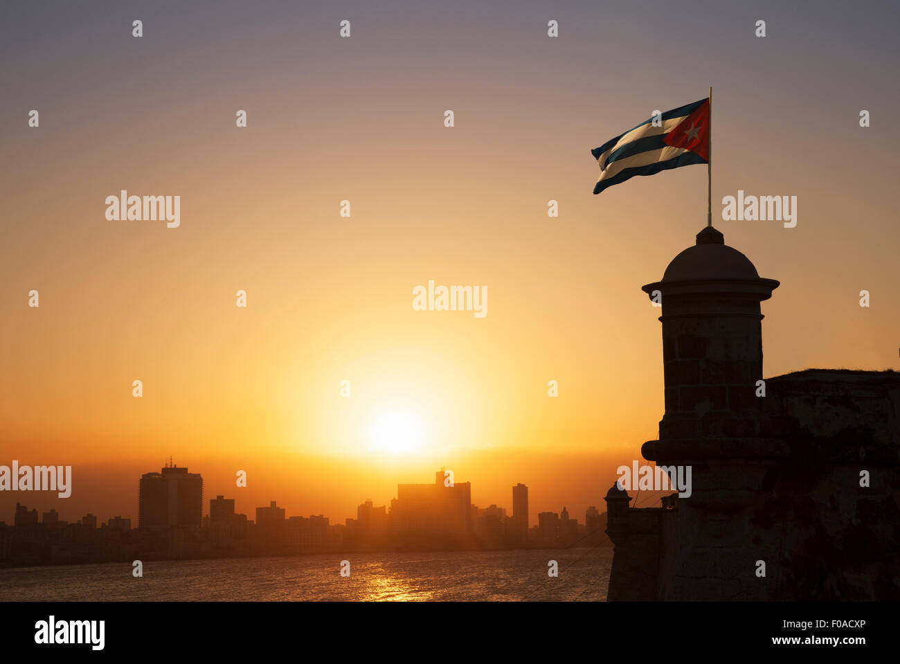 Cuban flag over the Fortress of El Morro at sunset, Havana, Cuba - Stock Image