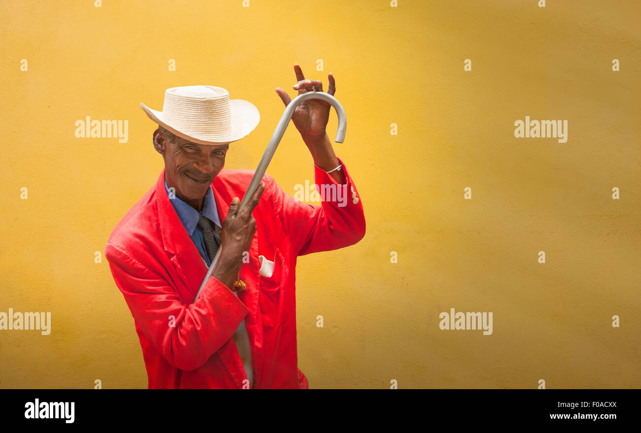 Mature male dancer poised in front of yellow wall, Havana, Cuba - Stock Image