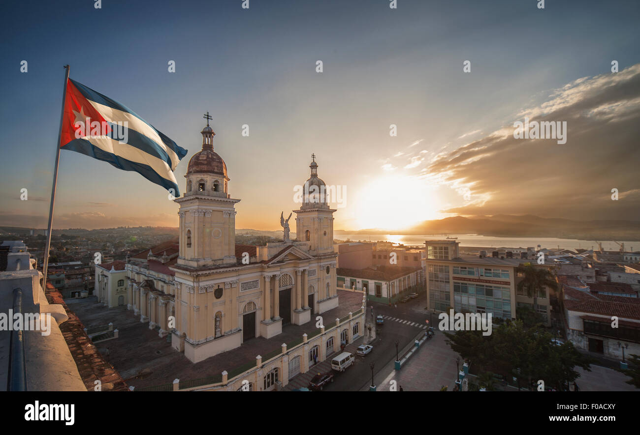 Cuban flag over Plaza de la catedral at sunset, Santiago de Cuba, Cuba - Stock Image