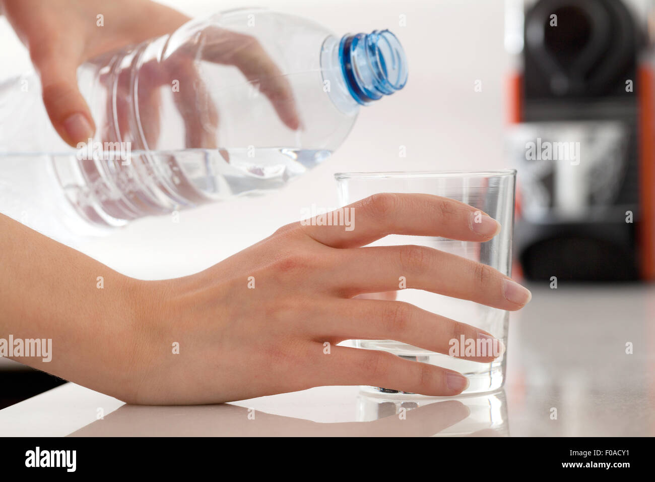 Female hands pouring bottled water into glass - Stock Image