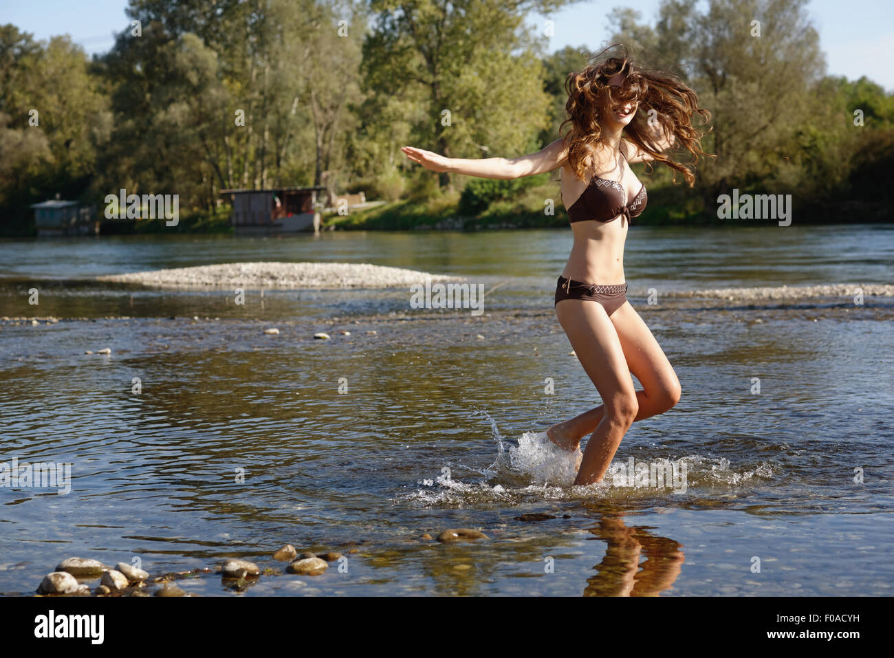 Young woman wearing a bikini splashing and playing in river - Stock Image