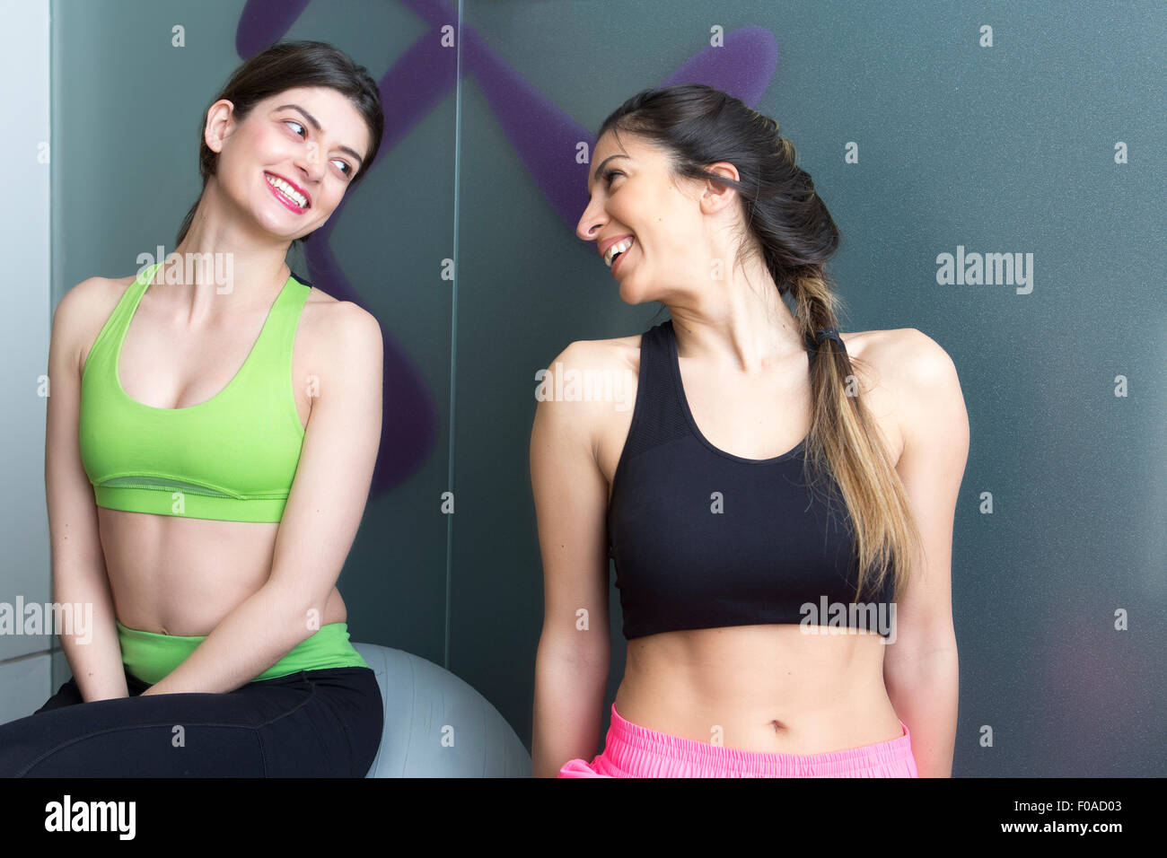 Two young women looking at each other and smiling in gym Stock Photo