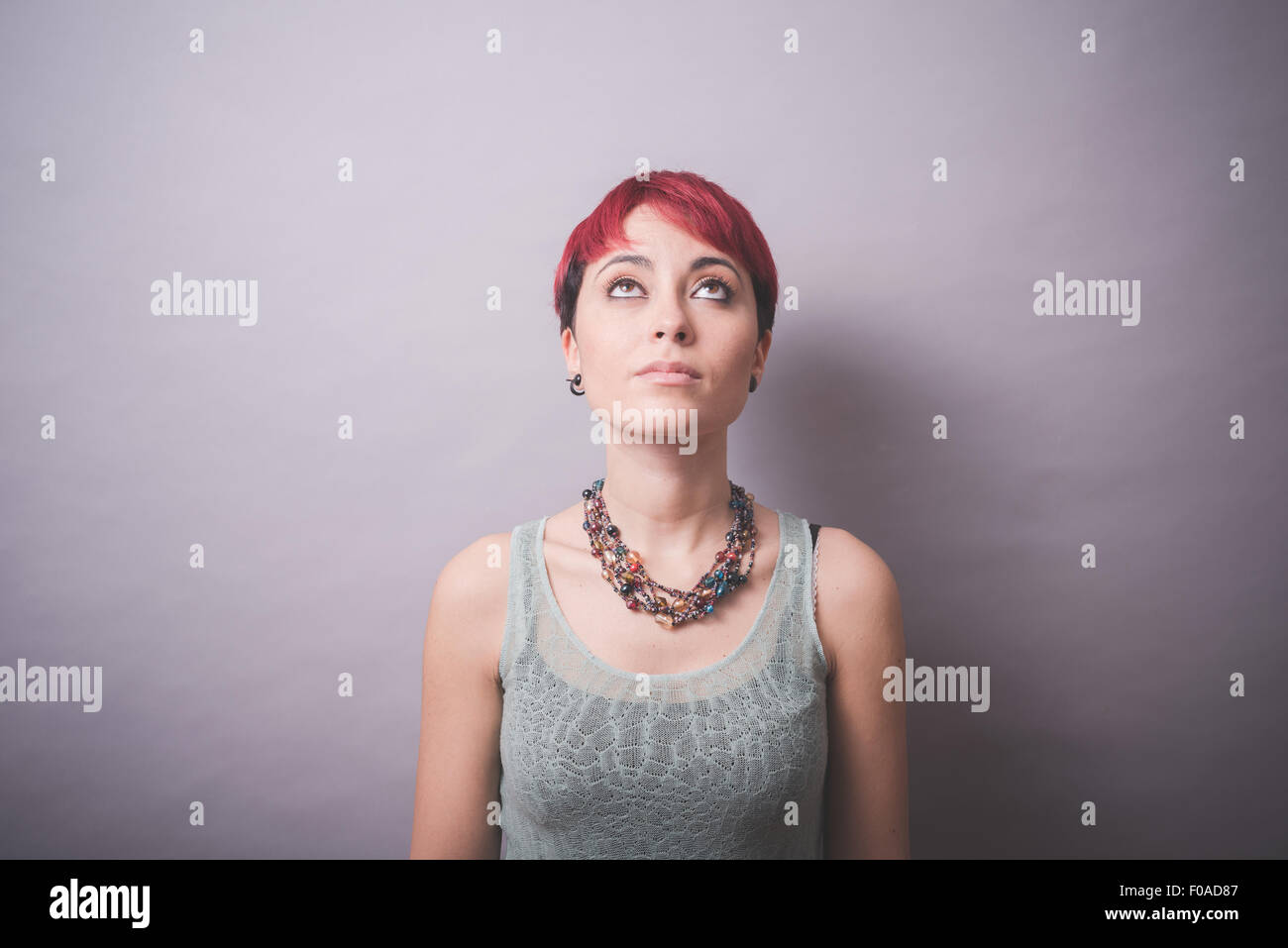 Studio portrait of young woman with short pink hair looking up - Stock Image