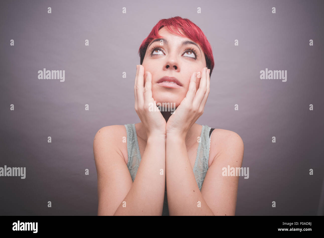 Studio portrait of young woman with short pink hair with hands on cheeks - Stock Image