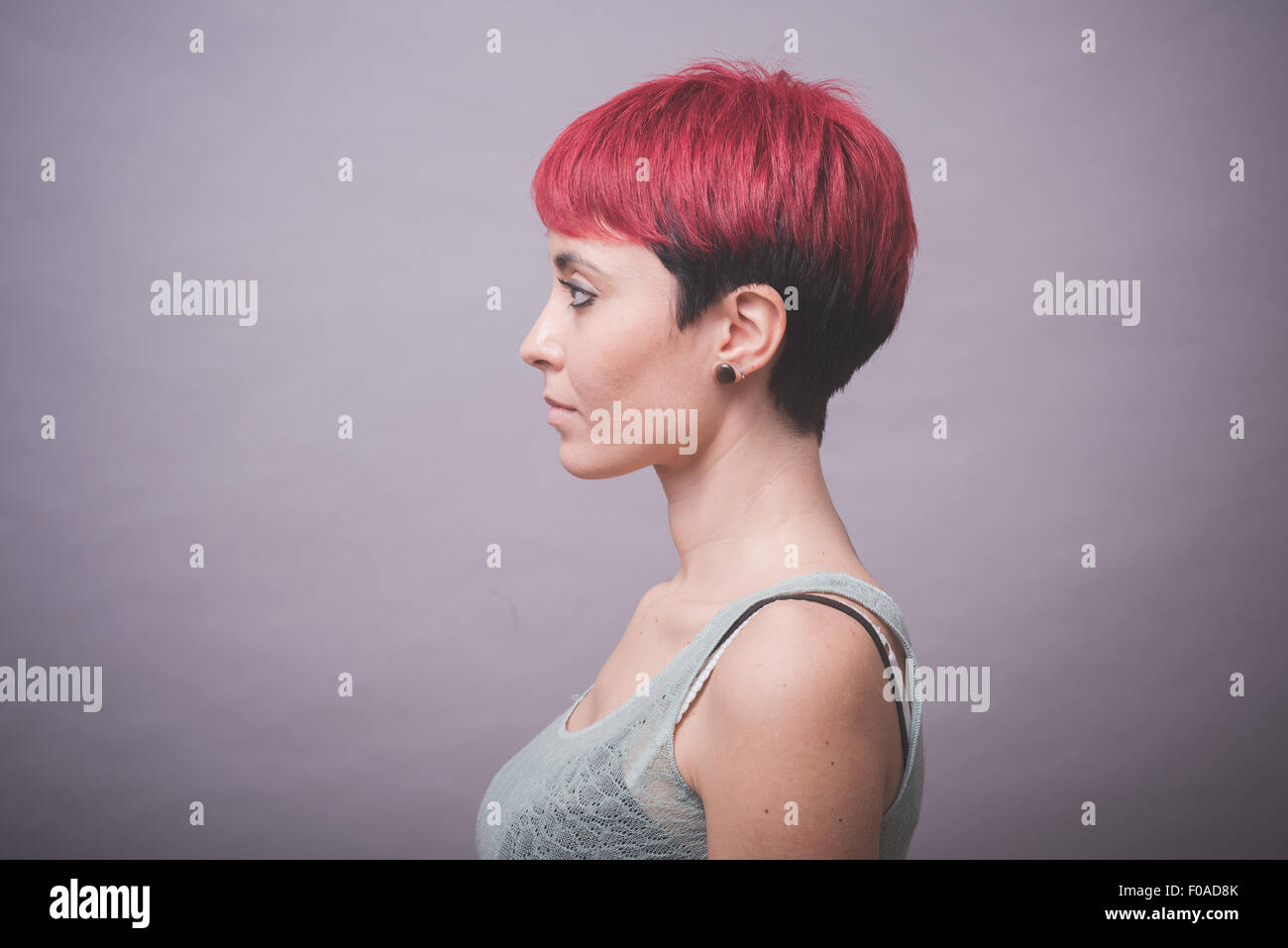Profile studio portrait of young woman with short pink hair with hands on cheeks - Stock Image