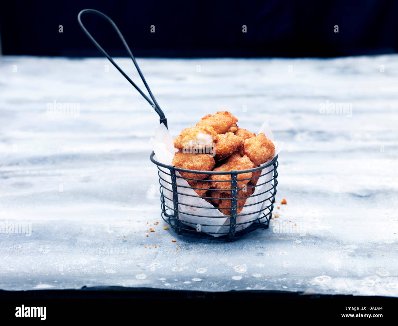 Frying basket full of breaded Scottish wholetail scampi Stock Photo
