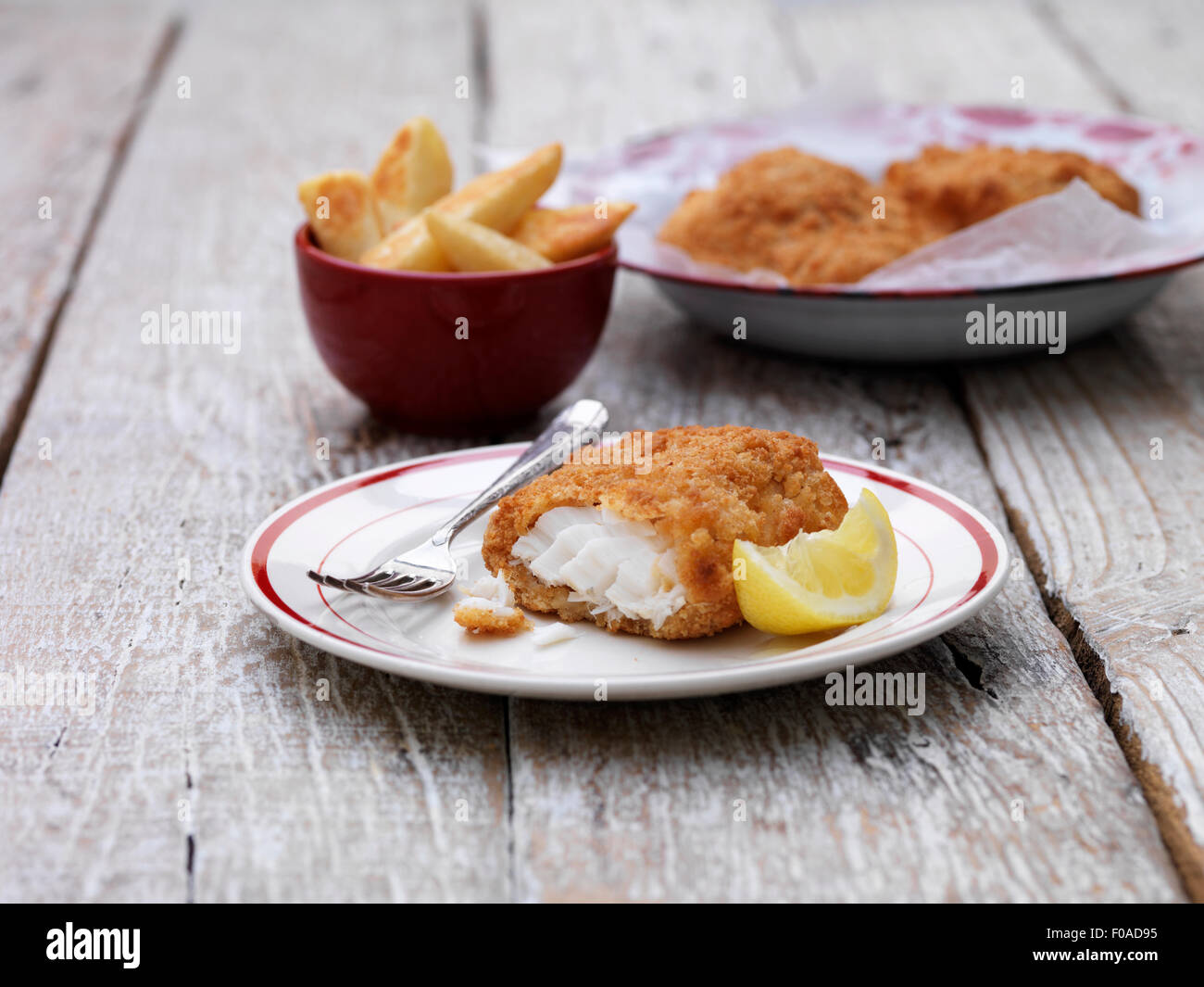 Breaded chunky cod with bowl of french fries on wooden table Stock Photo