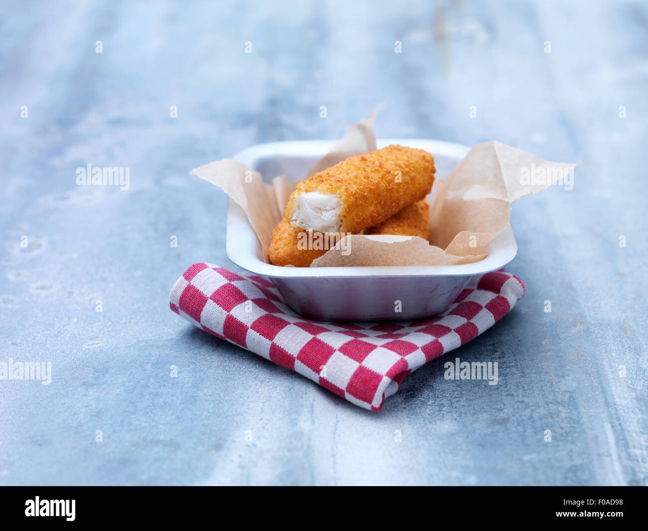 Fried chunky breaded cod fish fingers in baking tin on steel table - Stock Image