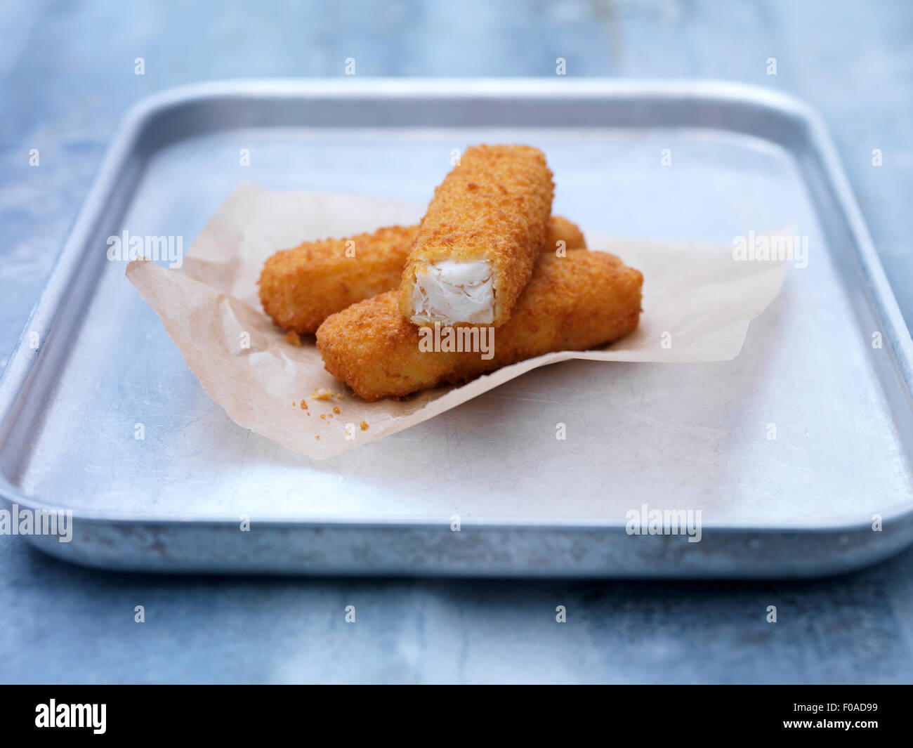 Baking tin with fried chunky breaded fish fingers on steel table - Stock Image