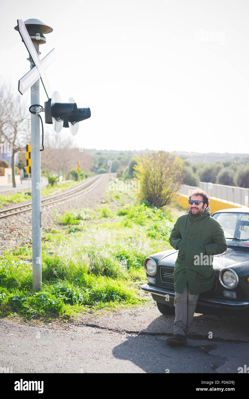 Mid adult man leaning against vintage car at railway crossing - Stock Image