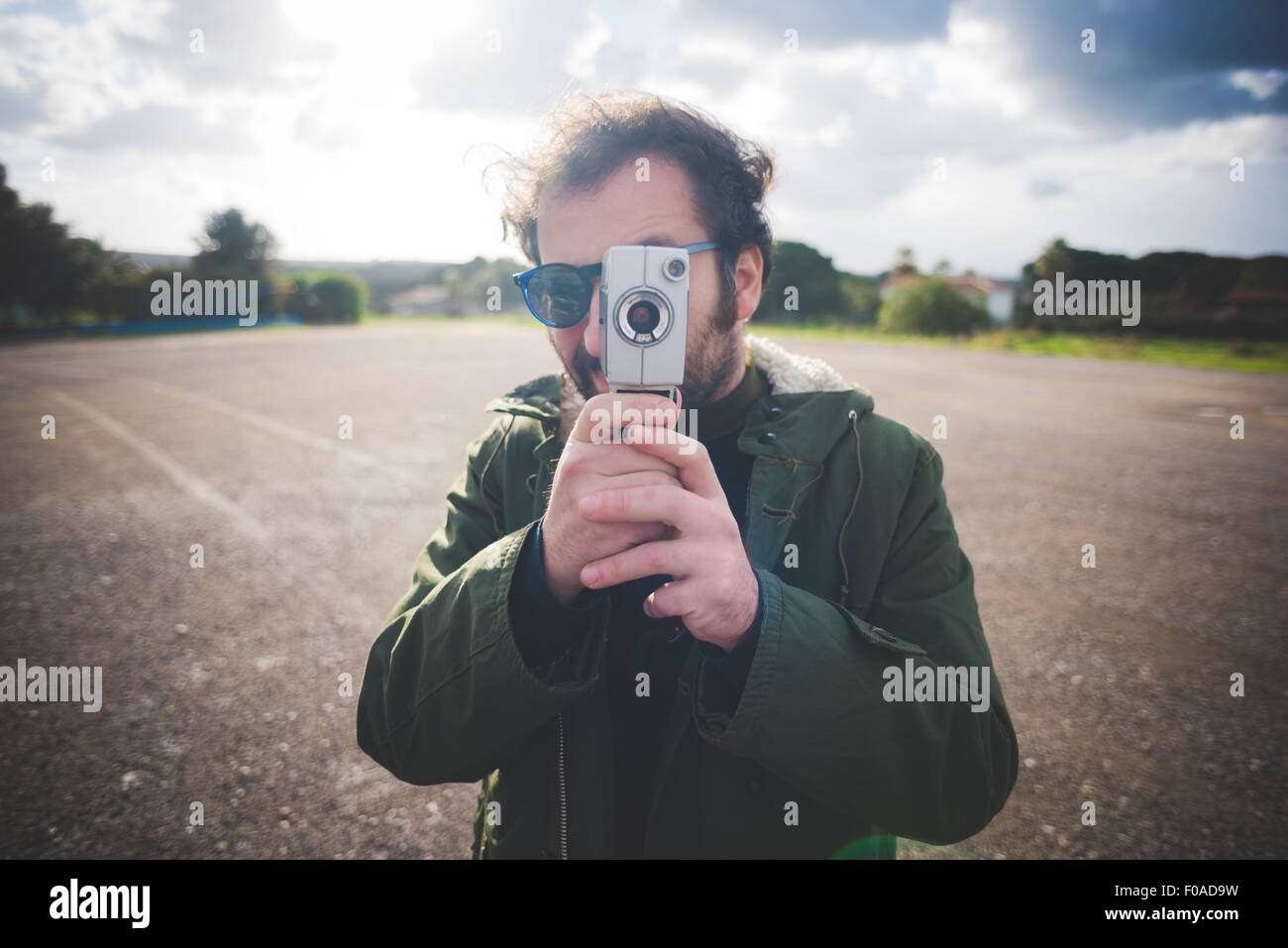 Portrait of mid adult man pointing vintage movie camera on waste ground - Stock Image