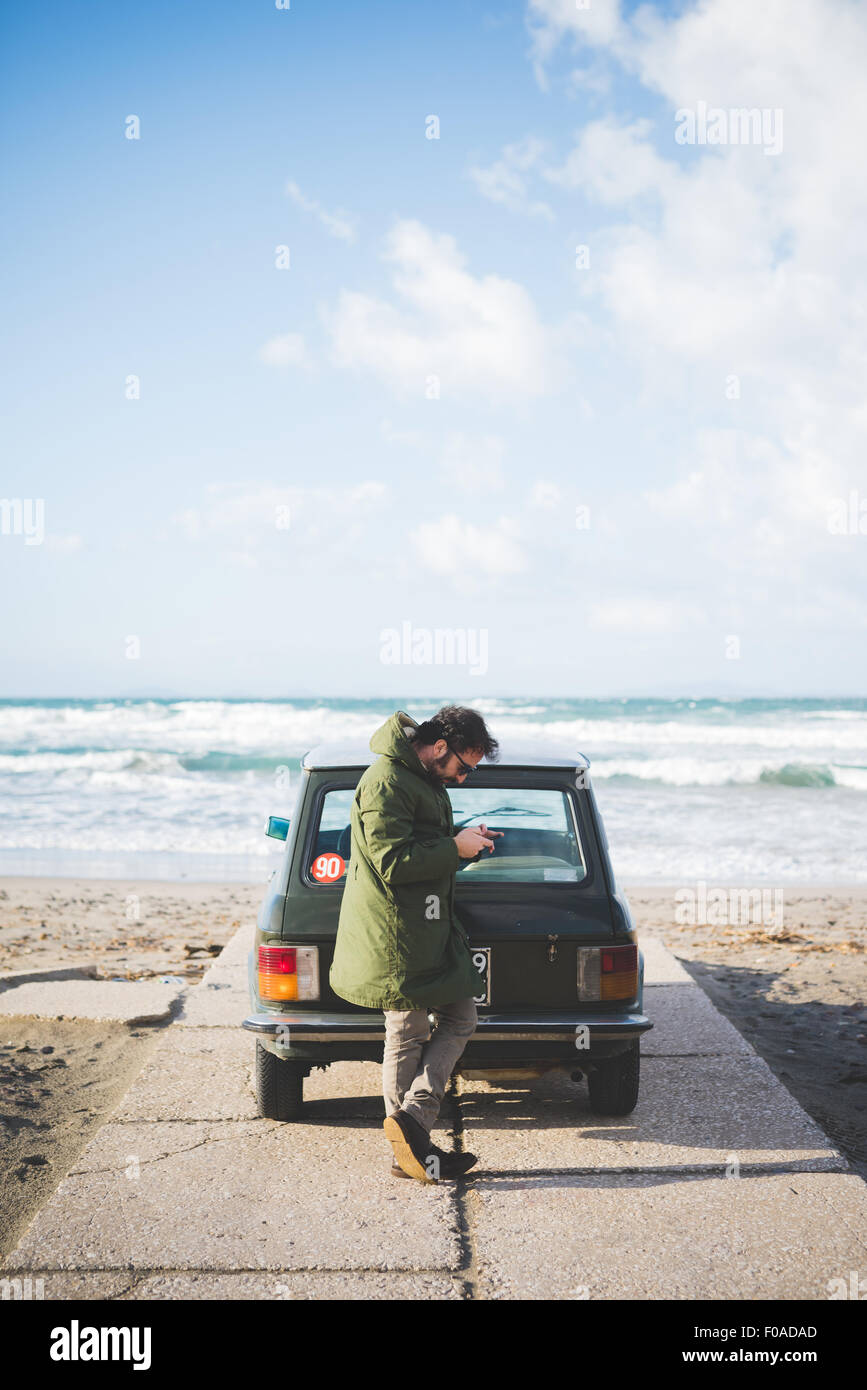 Man with vintage car parked on beach reading smartphone texts, Sorso, Sassari, Sardinia, Italy - Stock Image