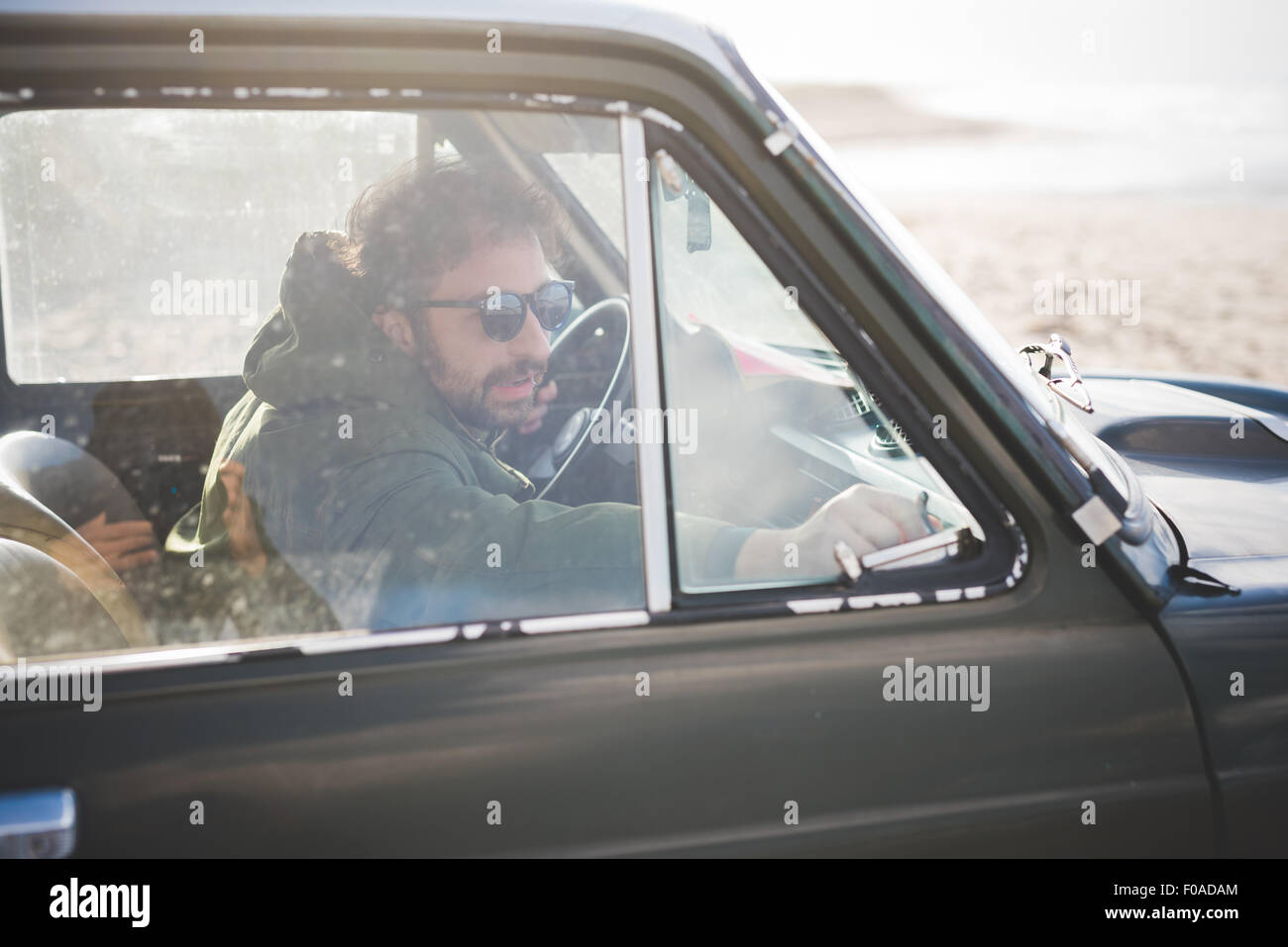 Man in parked vintage car lat beach fastening window - Stock Image